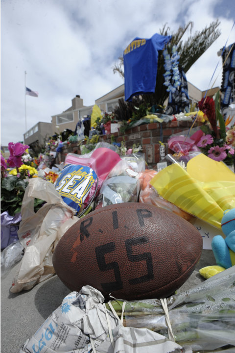 A football with Junior Seau's number sits in front of a memorial in the driveway of the house of former NFL star Junior Seau Thursday, May 3, 2012, in Oceanside, Calif.  Seau's death in Oceanside, in