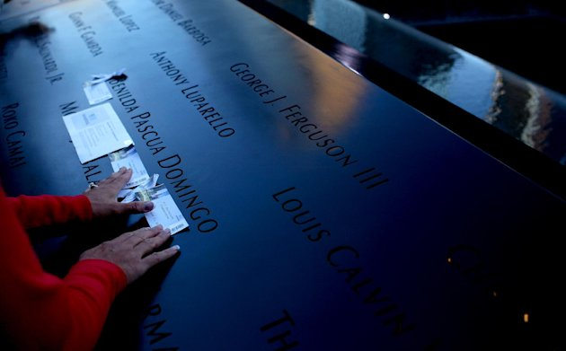 A family members of Belinda Pascua Domingo of New York arranges mementos under her name at the National September 11 Memorial in New York on the 11th anniversary of the attacks on the World Trade Cent