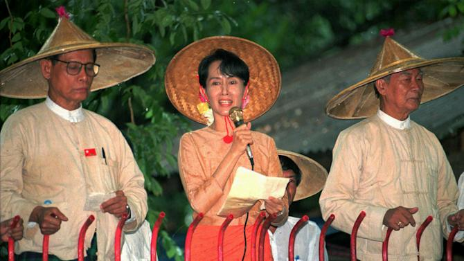 "FILE - In this June 16, 1996 file photo, pro-democracy leader Aung San Suu Kyi, center, speaks to supporters outside her home in Rangoon, Myanmar, as senior leaders in the National League for Democracy Tin Oo, left, and U Kyi Maung listen. President Barack Obama's historic visit to Myanmar on Monday, Nov. 19, 2012 is meant to show America's support for the country's transition to democracy. The White House has cautioned that Obama's trip to the former pariah state should not be viewed as a ""victory celebration"" but as an opportunity to press for urgent action still needed in Myanmar. Notably, freeing political prisoners and ending ethnic tension in remote areas.  (AP Photo/Stuart Isett, File)"