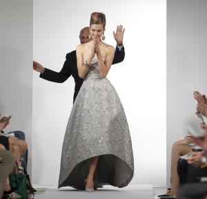 Fashion designer Oscar de la Renta waves as the final model in his show claps and walks the runway at the conclusion of the presentation of the Oscar de la Renta Spring 2013 collection at Fashion Week in New York, Tuesday, Sept. 11, 2012.  (AP Photo/Kathy Willens)