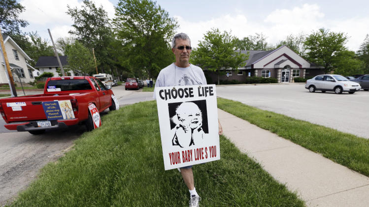Coalition for Life of Iowa member Ron Digmann walks in front of the Planned Parenthood clinic, Tuesday, May 21, 2013, in Cedar Rapids, Iowa. When the Coalition applied for tax-exempt status in 2008, the tiny group thought getting IRS approval would be easy. But the group faced months of delay, was ordered to provide details about its prayer events outside the clinic, and even directed to sign a sworn statement pledging it would not organize protests there. (AP Photo/Charlie Neibergall)
