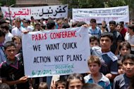 Syrian boys hold a banner about the international conference on the Syrian crisis being held in Paris during a demonstration after Friday prayers in Kfar Nubul in the northwestern province of Idlib