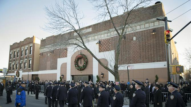 New York Police Department commanding officers enter the wake of officer Rafael Ramos at Christ Tabernacle Church, in the Glendale section of Queens, where he was a longstanding and deeply committed member, Friday, Dec. 26, 2014, in New York. Ramos was killed Dec. 20 along with his partner, Officer Wenjian Liu, as they sat in their patrol car on a Brooklyn street. The shooter, Ismaaiyl Brinsley, later killed himself. (AP Photo/John Minchillo)