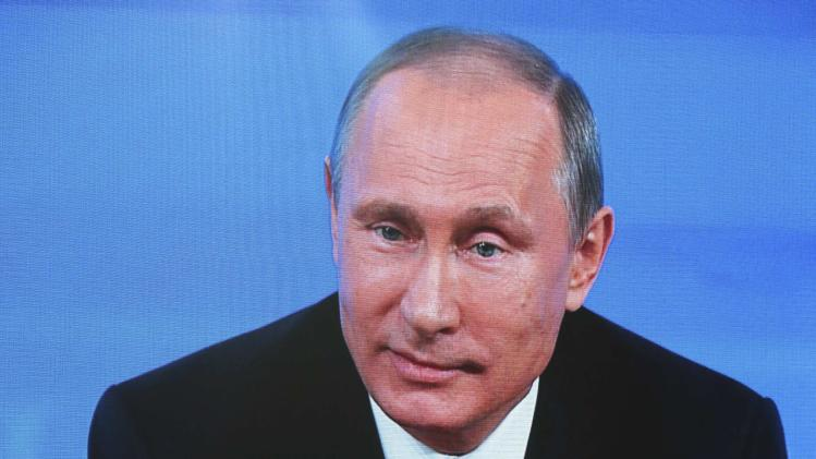 Russian President Putin is seen on a screen as he takes part in a televised news conference in Moscow