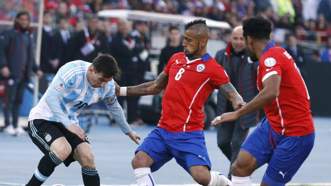 Argentina's Lionel Messi, Chile's Arturo Vidal and Chile's Jean Beausejour battle for the ball during their Copa America 2015 final soccer match at the National Stadium in Santiago