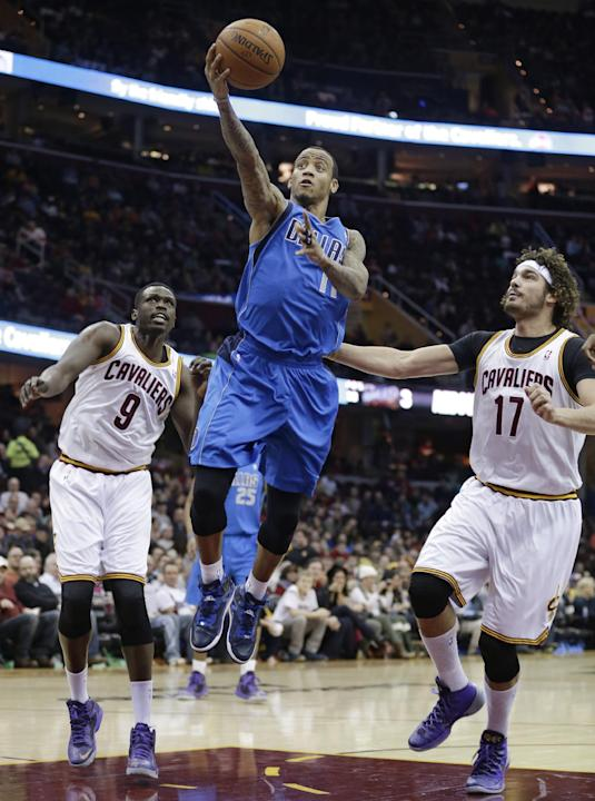CORRECTS FROM LOUL TO LUOL - Dallas Mavericks' Monta Ellis (11) shoots between Cleveland Cavaliers' Luol Deng, (9) from Sudan, and Cleveland Cavaliers' Anderson Varejao (17), from Brazil,