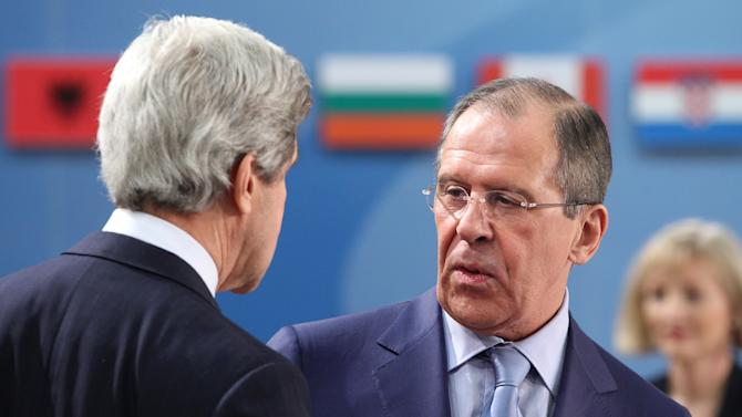 U.S. Secretary of State John Kerry, left, talks with Russia's Foreign Minister Sergey Lavrov, prior to the NATO-Russia Council during a NATO foreign ministers meeting at NATO headquarters in Brussels, Tuesday, April 23, 2013. (AP Photo/Yves Logghe)