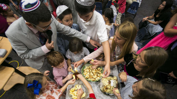 Rabbi Joshua Hearshen blesses children while they reach to dip apples into honey during the Erev Rosh Hashana, the eve of the Jewish New Year, family service held at Congregation Rodeph Sholom on Wednesday, Sept. 4, 2013 in St. Petersburg, Fla. The dipping of apples into honey is a traditional blessing to bring a sweet new year. (AP Photo/The Tampa Bay Times, Will Vragovic)