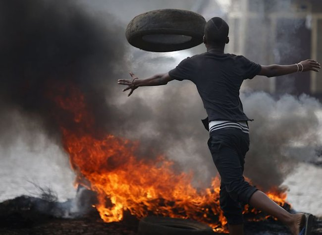 A protester sets up a barricade during a protest against Burundi President Pierre Nkurunziza and his bid for a third term in Bujumbura, Burundi, May 2...