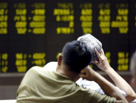 Investors watch an electronic board showing stock information at a brokerage office in Beijing