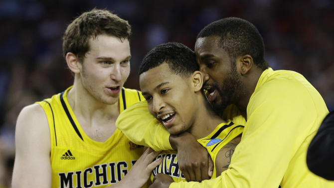 Michigan's Nik Stauskas (11), Trey Burke (3) and Corey Person celebrate after beating Kansas  87-85 in overtime of a regional semifinal game in the NCAA college basketball tournament, Friday, March 29, 2013, in Arlington, Texas. (AP Photo/David J. Phillip)