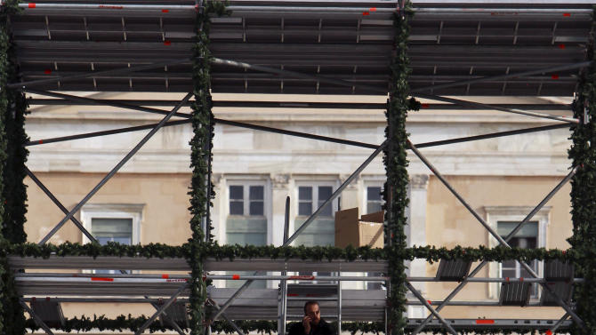 A worker speaks on his cellphone as he sits on scaffolding erected to display Christmas decorations, , with the Greek parliament in the background at the Athens' main Syntagma square on Friday, Dec. 7, 2012. Greece's economy shrank by 6.9 percent in the third quarter of the year, compared with the same period in 2011. Separately, Greece's debt management agency has announced it will seek to raise euro 3.75 billion ($4.9 billion) in treasury bills next week. (AP Photo/Thanassis Stavrakis)