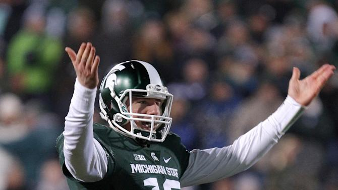 Michigan State quarterback Connor Cook encourages the crowd during the fourth quarter of an NCAA college football game against Penn State, Saturday, Nov. 28, 2015, in East Lansing, Mich. Michigan State won 55-16. (AP Photo/Al Goldis)