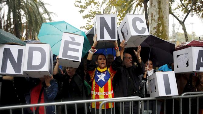 """People form the word """"Independence"""" supporting former Catalan vice-president Joana Ortega as she arrives at Catalonia's Supreme Court to testify for the 9N consultation"""