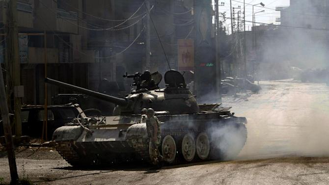 A military tank is seen during clashes that erupted between followers of a radical Sunni cleric Sheik Ahmad al-Assir and Shiite gunmen, in the southern port city of Sidon, Lebanon, Monday, June 24, 2013. Lebanese troops battled heavily armed followers of a hard-line Sunni cleric holed up in a mosque complex in a southern port city on Monday, the second day of fighting that has left at least 16 soldiers dead, the military said. (AP Photo/Mohammed Zaatari)