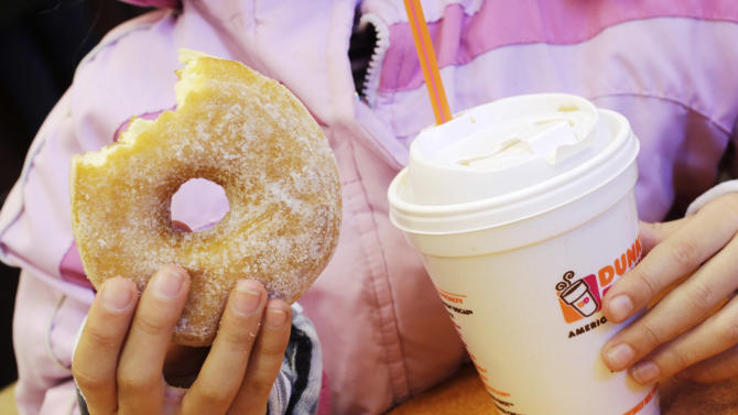 """FILE - In this Feb. 14 2014 file photo, a girl holds a doughnut and a beverage at a Dunkin' Donuts in New York. Dunkin' Brands CEO Nigel Travis said in a phone interview Thursday, July 24, 2014, that the company is pushing to get its cashiers to """"upsell"""" to afternoon customers. It's part of an effort to increase sales after stores have emptied out after the morning rush. (AP Photo/Mark Lennihan, File)"""