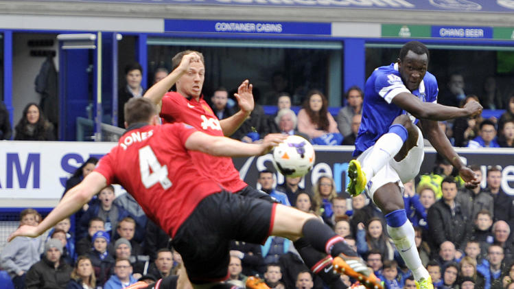 Everton's Romelu Lukaku right, has his shot handled by Manchester United's Phil Jones left, which awards Everton a penalty during their English Premier League soccer match at Goodison Park in Liverpool, England, Sunday April 20, 2014. (AP Photo/Clint Hughes)