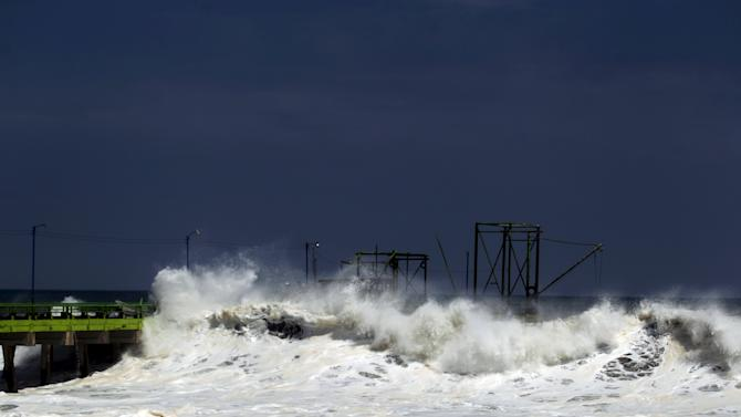 A wave crashes on a fishing dock at La Libertad