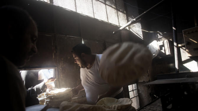 In this Saturday, Sept. 22, 2012 photo, a Syrian man works at a bakery in the Saif al Dawla neighborhood of Aleppo, Syria. (AP Photo/ Manu Brabo)