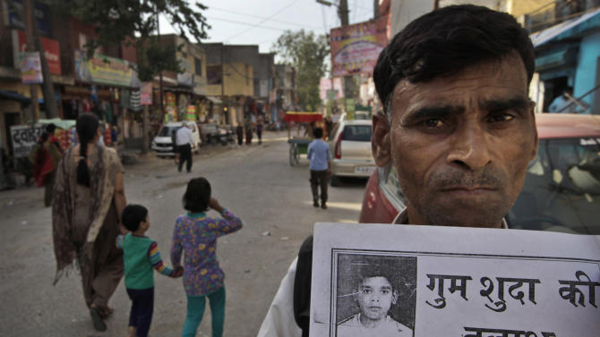 In this Monday, March 25, 2013, photo, Kunwar Pal, 45, shows a poster of his missing son Ravi Kumar, 12, who went missing three years ago, in New Delhi, India. Kumar is among the more than 90,000 children who go missing in India each year. More than 34,000 of them are never found, the government said last year. (AP Photo/Manish Swarup)