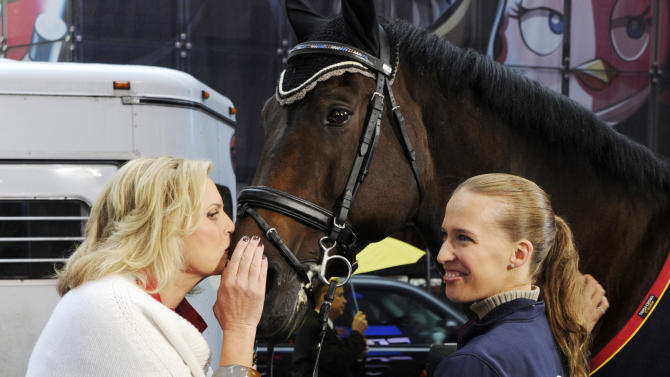"""This photo released by Good Morning America, Wednesday, Oct. 10, 2012, shows Ann Romney, wife of Republican presidential nominee Mitt Romney, left, planting a kiss on Lord Ludger while his rider Rebecca Hart watches on the set of the television show in New York. Romney said Wednesday that her love of horses helped her overcome her fear that multiple sclerosis would put her in a wheelchair. She was guest hosting ABC's """"Good Morning America"""" when she spoke about her depression after receiving the diagnosis 14 years ago. Hart recently won the USEF National Para-Equestrian Championship. (AP Photo/ABC, Ida Mae Astute)"""