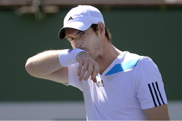 Andy Murray, of Great Britain, wipes his mouth after winning a game against Milos Raonic, of Canada, during a fourth round match at the BNP Paribas Open tennis tournament, Wednesday, March 12, 2014, i
