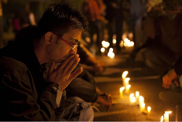 An Indian participates in a candle-lit vigil to mourn the death of a gang rape victim in New Delhi, India, Saturday, Dec. 29, 2012. Indian police charged six men with murder on Saturday, adding to acc