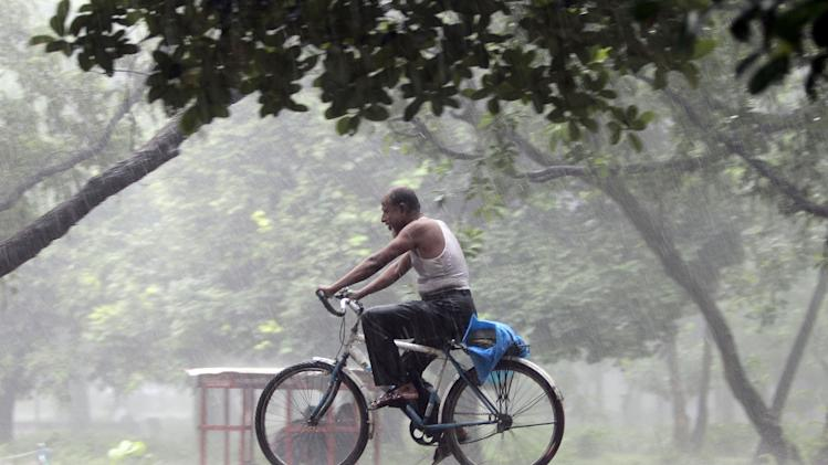 An elderly Bangladeshi man rides a bicycle in the rain in Dhaka, Bangladesh, Saturday, Aug. 23, 2014. (AP Photo/A.M. Ahad)