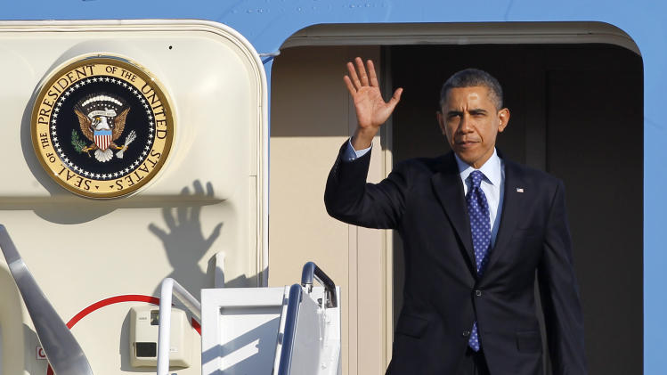 President Barack Obama waves as he walks off Air Force One at Andrews Air Force Base, Md., Thursday, Feb. 14, 2013, upon returning from Decatur, Ga., where he spoke of his education plans., following his State of the Union address.  (AP Photo/Ann Heisenfelt)