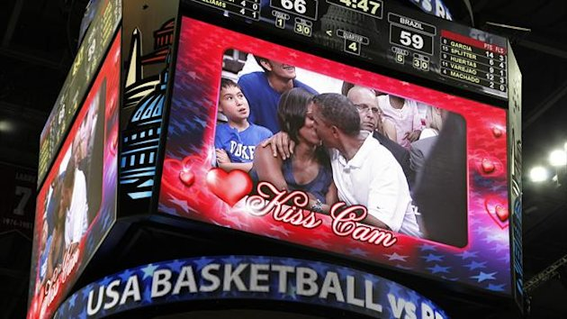 U.S. President Barack Obama and first lady Michelle Obama are shown kissing on the &quot;Kiss Cam&quot; screen during a time out in the Olympic basketball exhibition game  (Reuters)