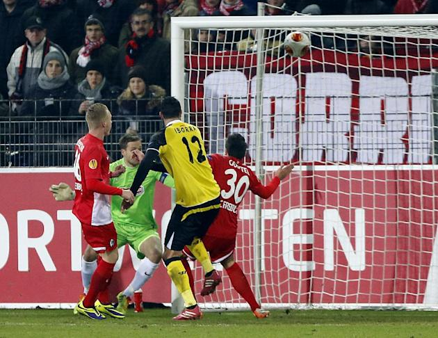 Sevilla's Vicente Iborra, center, scores his side's opening goal during a Group H Europa League match between SC Freiburg and Sevilla FC in Freiburg, Germany, Thursday, Dec.12, 2013
