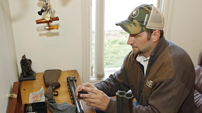 In this photo taken on Friday, April 12, 2013, Gaspar Perricone cleans one of his guns at his home in Denver.  Perricone co-founded The Bull Moose Sportsmen's Alliance, a group that took the unusual step earlier this month of releasing a poll that showed wide support among hunters for universal background checks. Most public polls have shown about 90 percent of voters support such a measure. (AP Photo/Ed Andrieski)