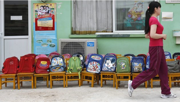 A woman walks past school bags that have been placed on chairs at a kindergarten yard in a village, in the outskirts of Beijing
