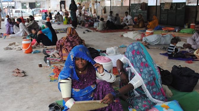 FILE - In this June 25, 2015 file photo, people sit outside a local hospital where hundreds of people are admitted suffering from heatstroke and dehydration due to sever weather in Hyderabad, Pakistan. Because of man-made global warming and a strong El Nino, Earth's wild weather this year is bursting the annual heat record, the World Meteorological Organization announced Wednesday, Nov. 25.  (AP Photo/Pevaiz Masih, File)