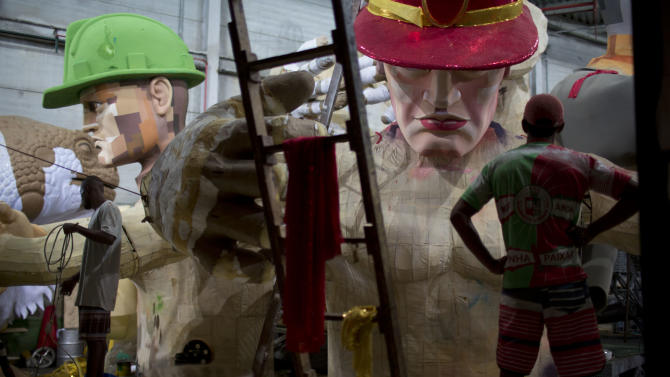 In this photo taken Tuesday, Jan. 22, 2013, men work on a Carnival float at the Grande Rio Samba school in Rio de Janeiro, Brazil. Yet it's from warehouses like this one that Rio's over-the-top glitz-and-glam Carnival parades emerge, as they will Monday night for the final round of a two-day performance. The internationally renowned competition between 12 elite samba groups dazzles more than a billion spectators in person and on TV for two days, but it takes nearly a year and hundreds of workers, many of them volunteers, to pull each one together. (AP Photo/Felipe Dana)
