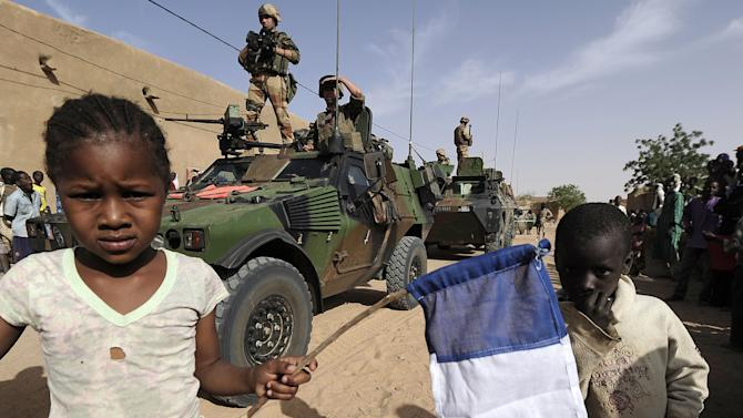 Locals welcome French soldiers with a French flag in Bourem, northen Mali, Sunday, Feb. 17, 2013. Mali's military detained eight Arab men last week in Timbuktu, raising fears of further reprisals against the region's Arab minority whose members are accused of having supported the al-Qaida-linked groups which overran northern Mali last year. (AP Photo /Pascal Guyot, Pool)