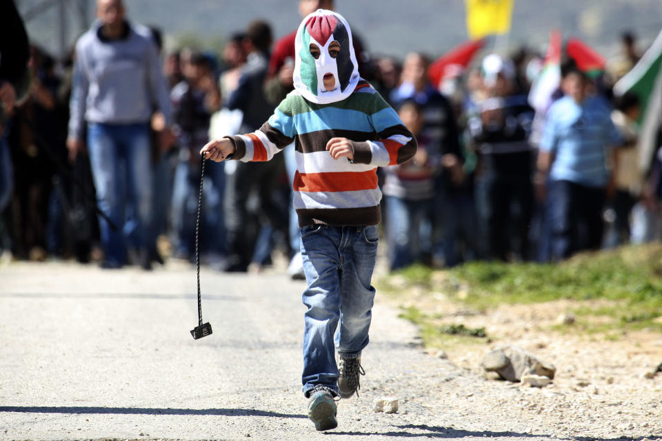 A masked Palestinian youth hurls stones at Israeli security forces during a protest in the village of Kufr Qaddum near the Israeli settlement of Kdumim, in the northern West Bank, Friday, March 9, 2012. (AP Photo/Nasser Ishtayeh)