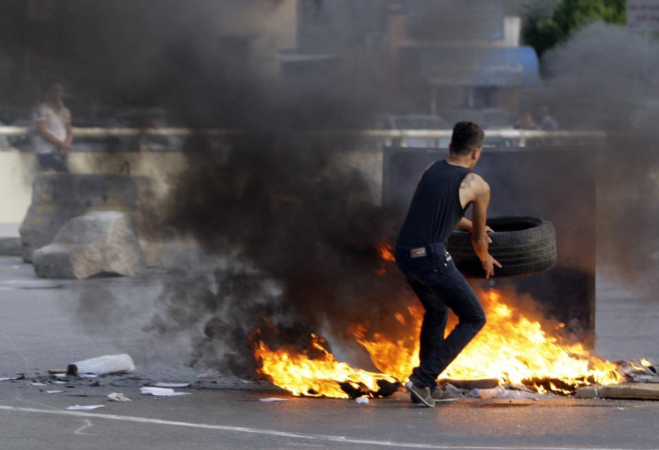 FILE - In this Tuesday, May 22, 2012 file photo, a Lebanese Shiite Muslim blocks the street in a southern suburb of Beirut, Lebanon, to protest against Syrian rebels kidnapped of 12 Lebanese Shiite pilgrims in the Syrian northern province of Aleppo. (AP Photo/Bilal Hussein, FIle)