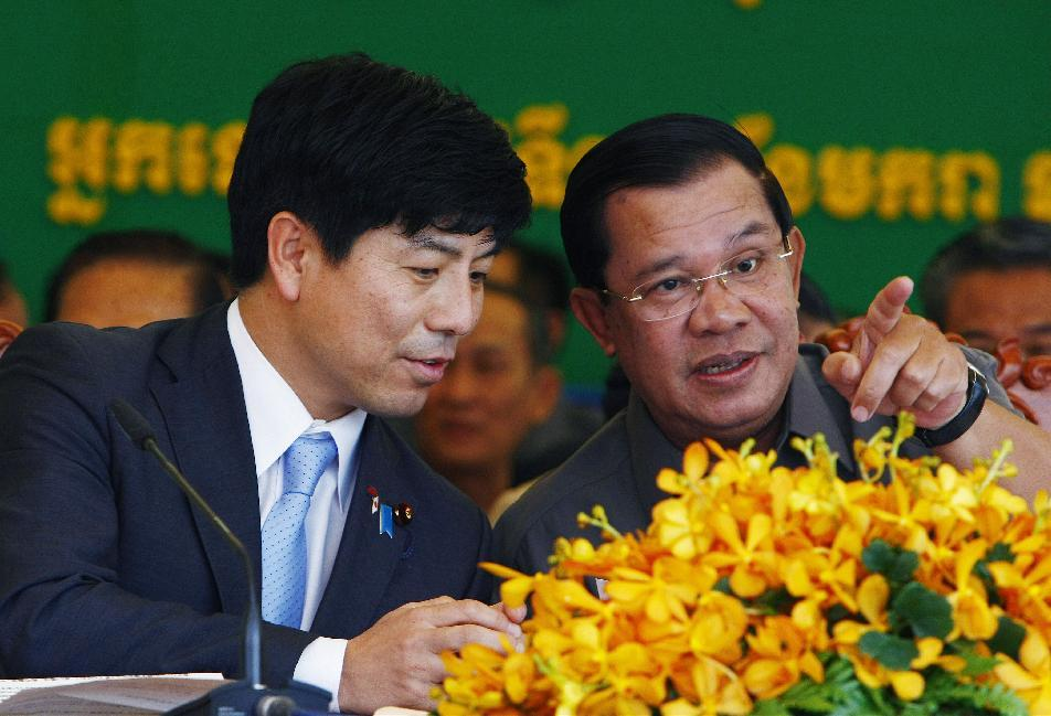 Cambodia's Prime Minister Hun Sen, right, gestures as he is seated with Kazuyuki Nakane, left, Japanese Parliamentary Vice-Minister for Foreign...