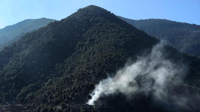 Smoke rises from Afghan houses reportedly burned by Taliban militants during an ongoing anti-Taliban operation in eastern Kunar province on January 17, 2015