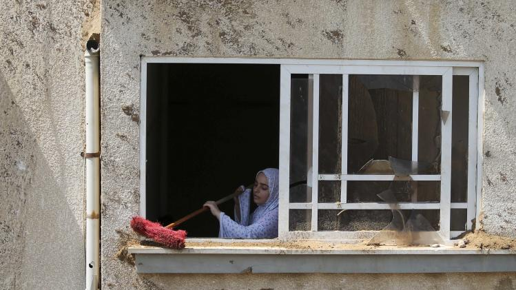 Palestinian woman cleans the edge of her house's window, which witnesses said was damaged in an Israeli air strike, in Gaza City