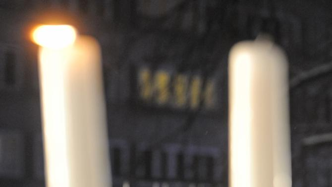 People gather to watch the lightning of  the first candle celebrating the beginning of Hanukkah, the Jewish festival of lights, on Grzybowski square in Warsaw, Poland, Saturday, Dec. 8, 2012. (AP Photo/Alik Keplicz)