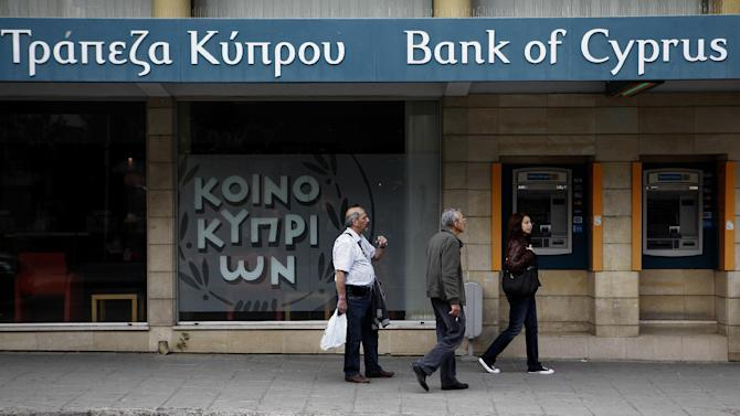 People pass by a branch of the bank of Cyprus in central capital Nicosia, Cyprus, on Saturday, March 30, 2013. Big depositors at Cyprus' largest bank may be forced to accept losses of up to 60 percent, far more than initially estimated under the European rescue package to save the country from bankruptcy, officials said Saturday. (AP Photo/Petros Karadjias)