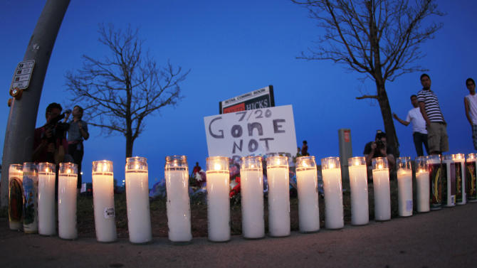 """As night falls, candles sit iluminated along the sidewalk in front of a makeshift memorial for the victims of a mass shooting at the Century 16 theatre east of the Aurora Mall in Aurora, Colo., on Friday, July 20, 2012. Authorities report that 12 died and more than three dozen people were shot during an assault at the theatre during a midnight premiere of """"The Dark Knight."""" (AP Photo/David Zalubowski)"""