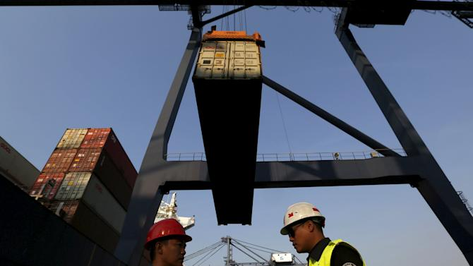 Workers talks as a crane moves a container at Koja Container Terminal near Tanjung Priok port in Jakarta