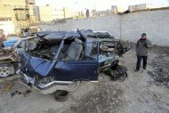 An Iraqi man inspects damaged vehicles in a car bomb attack in Baghdad, Iraq, Monday, Dec. 16, 2013. Iraqi officials say bombings in and around Baghdad have killed and wounded tens of people. (AP Photo/Karim Kadim)