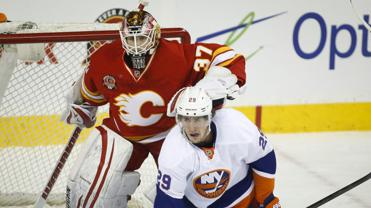 New York Islanders' Brock Nelson, right, gets pushed to the ice by Calgary Flames goalie Joni Ortio, from Finland, during the first period of an NHL hockey game Friday, March 7, 2014, in Calgary, Alberta. (AP Photo/The Canadian Press, Jeff McIntosh)