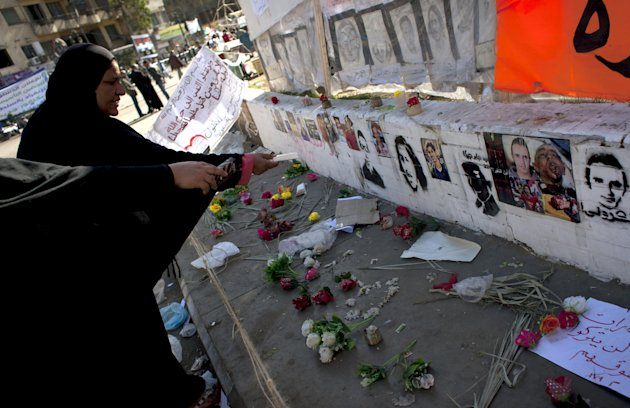 "Two Egyptian women protesters pay their respects in front of a spot designated for pictures of protesters killed during the Egyptian revolution and verses of Quran that reads ""do not kill the soul tha"