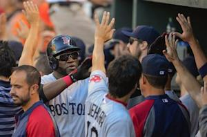 Red Sox designated hitter Ortiz is greeted by teammates after scoring in the ninth inning against Orioles relief pitcher Johnson during their MLB game in Baltimore