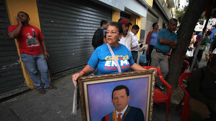 A woman holds a painting of President Hugo Chavez as supporters gather around Bolivar square after his return to the country in Caracas, Venezuela, Monday, Feb. 18, 2013.  Chavez returned to Venezuela early Monday after more than two months of medical treatment in Cuba following cancer surgery. The government didn't offer an explanation as to why Chavez made his surprise return while he is undergoing other treatments that have not been specified.(AP Photo/Fernando Llano)